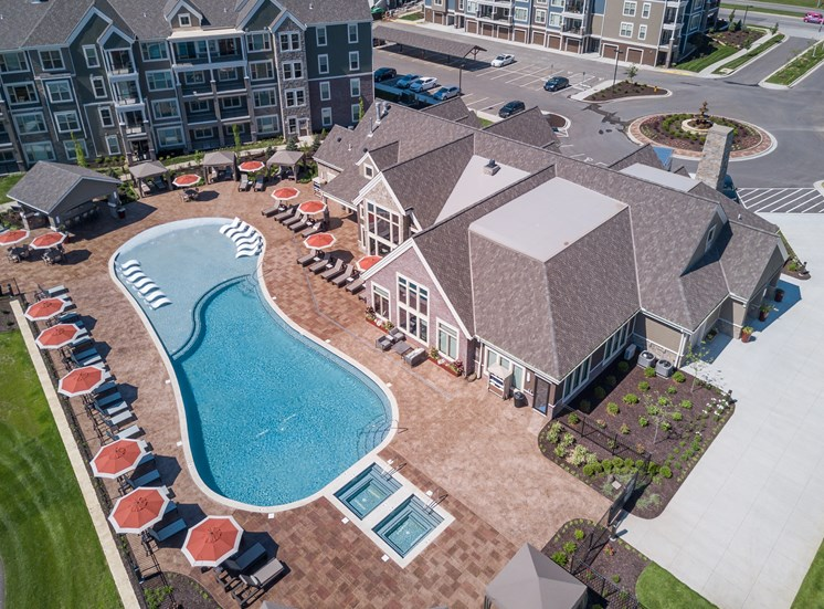 Lenexa Apartments-Waterside Residences at Quivira Apartments Drone View Of Pool And Double Jacuzzis Surrounded by Lounging Areas