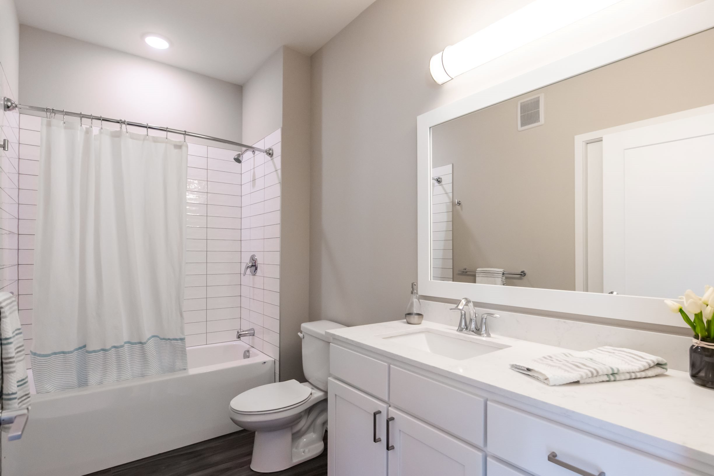 Townhome Bathroom with white cabinetry, subway tiled shower