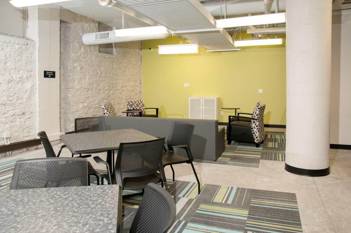 Common Room with Lounge Seating and Tables of The Cameron North Loop Apartments