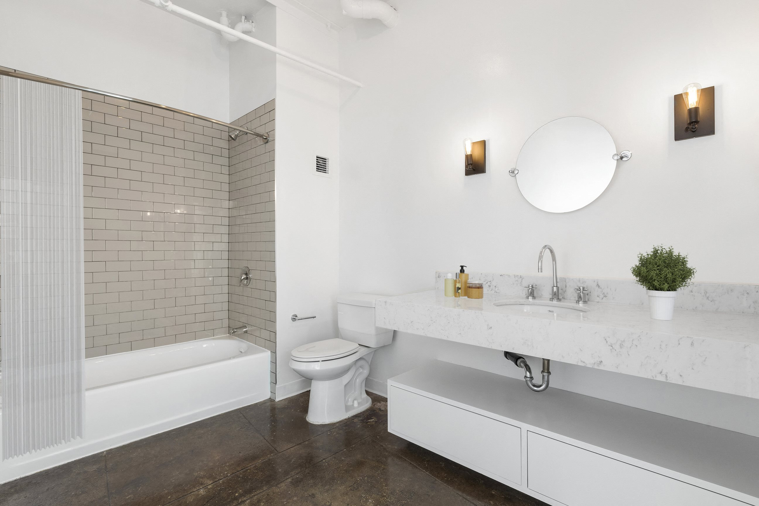 Downtown LA Apartments-San Fernando Building Lofts Bathroom with Gorgeous Modern Countertops, Large Shower Area, and Floating Cabinet Storage