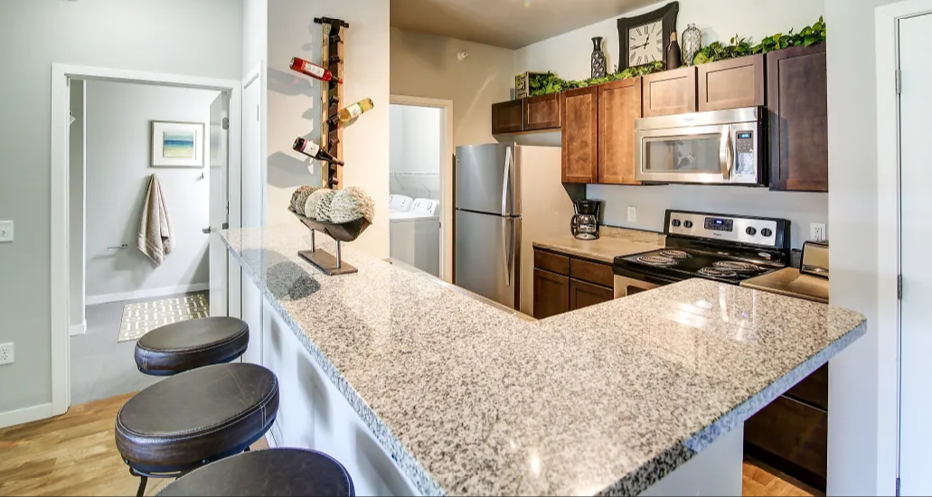 Kitchen with brown cabinets, brown speckled counter tops, and stainless steal appliances. There is also a peninsula with bar stools set up by it. Grey walls and hardwood-like flooring.