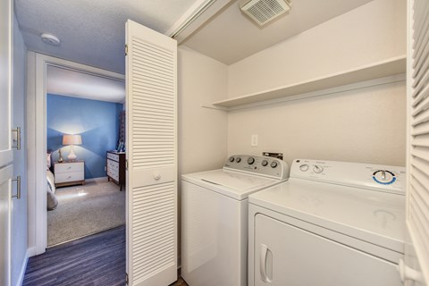 Full Size In Unit Washer Dryer with View of Bedroom and White Walls
