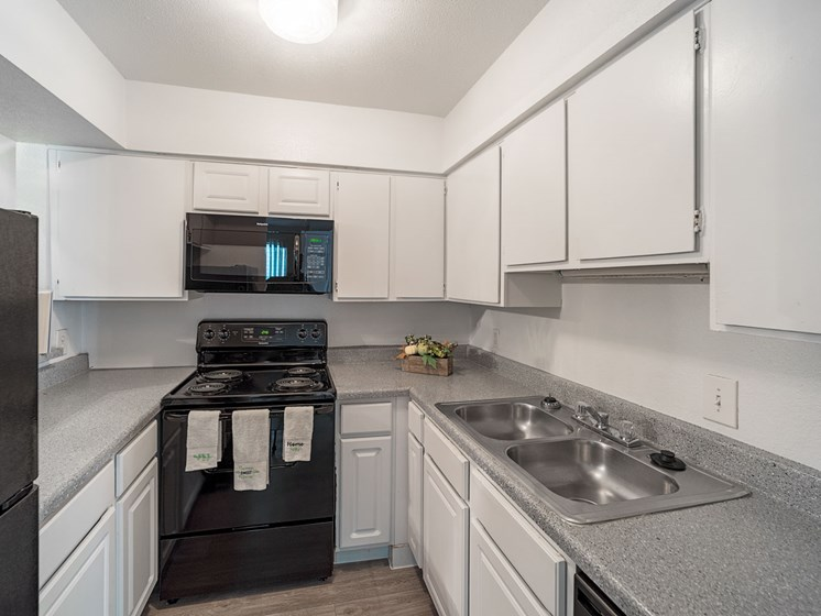 Updated Kitchen With Black Appliances at Carelton Courtyard Apartments, Galveston, 77550