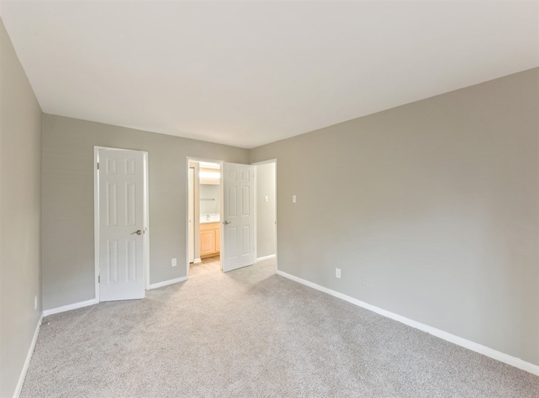 Model bedroom with closet, bathroom, carpet, and modern two tone paint.