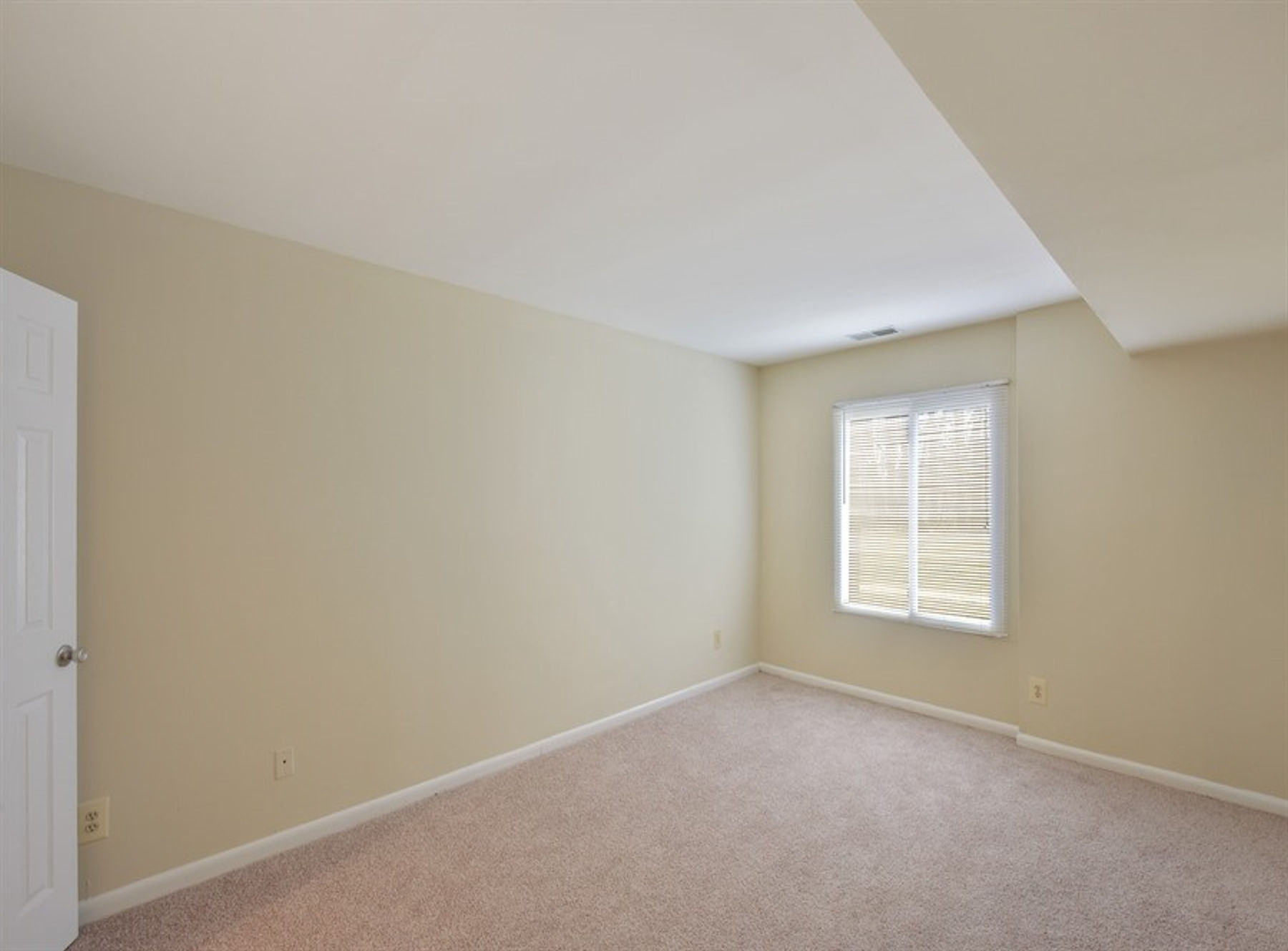 Model bedroom with large window, carpeting, and modern paint.