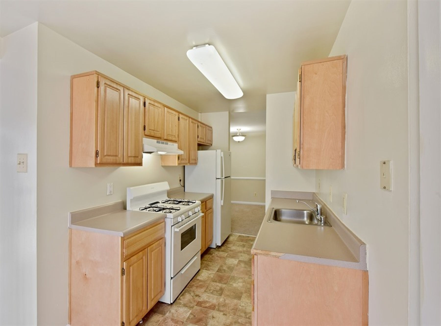 Model kitchen with custom cabinets, white appliances, and vinyl flooring.