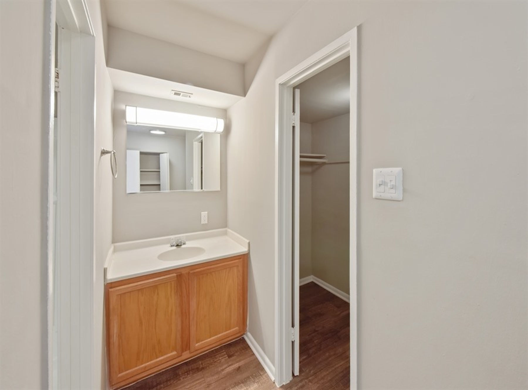Model bathroom with large mirror.