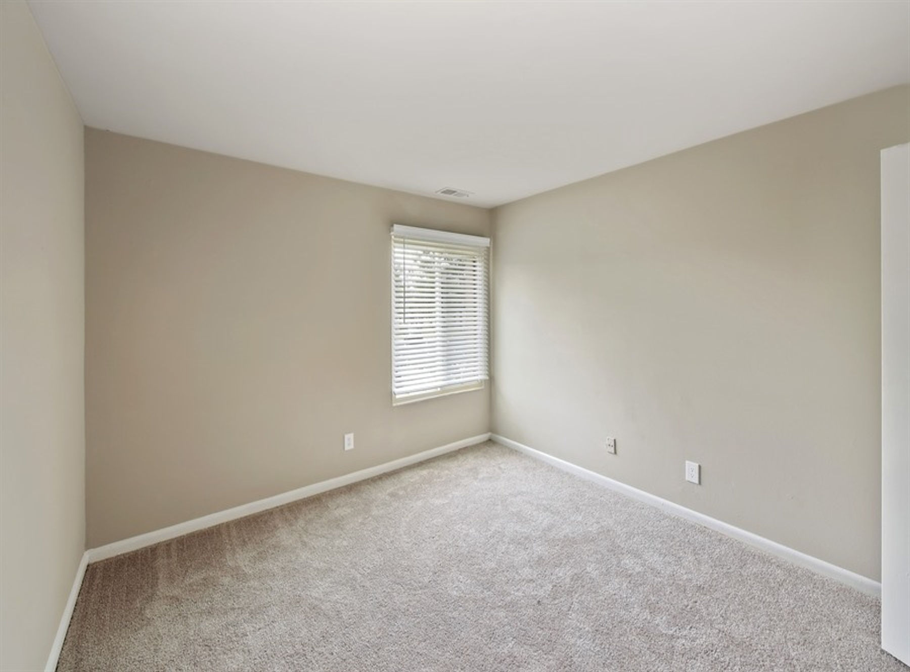 Model bedroom with large window and carpet.