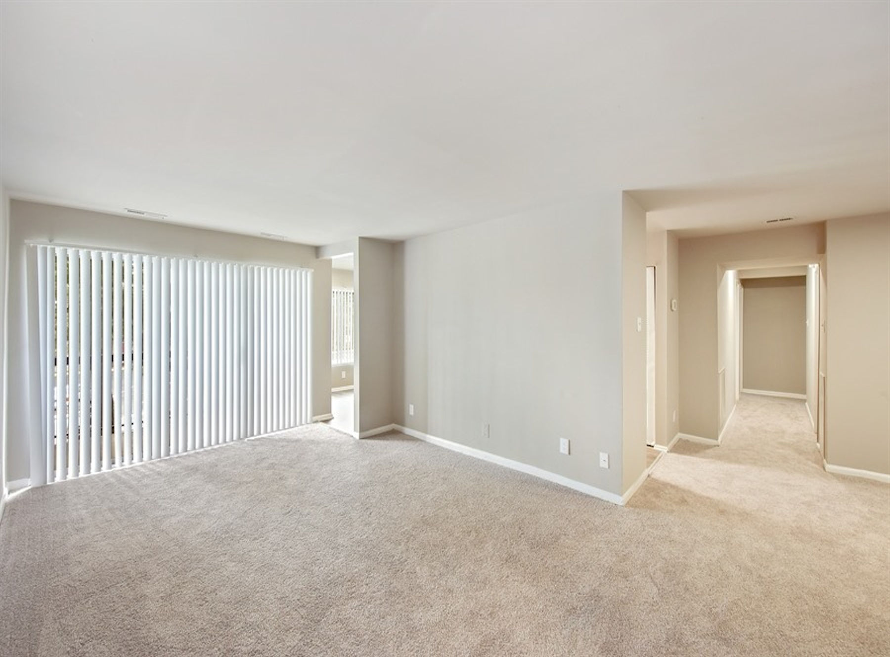Model living room with large windows, private patio/balcony, and carpet.