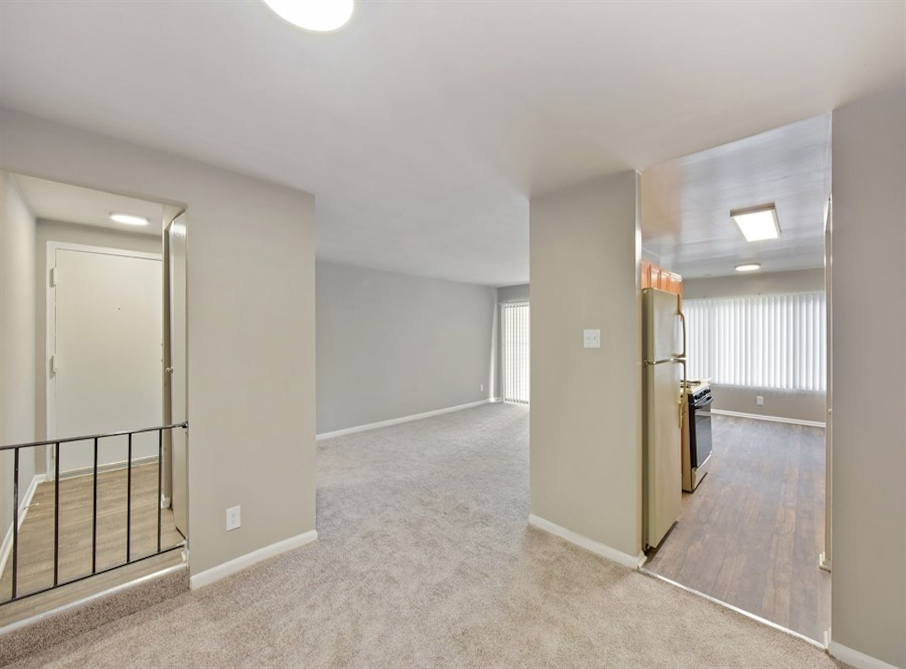 Model entry with vinyl flooring, modern paint, and carpet.