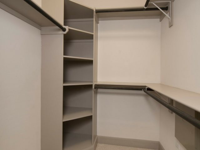 Walk-in closets with wood shelving