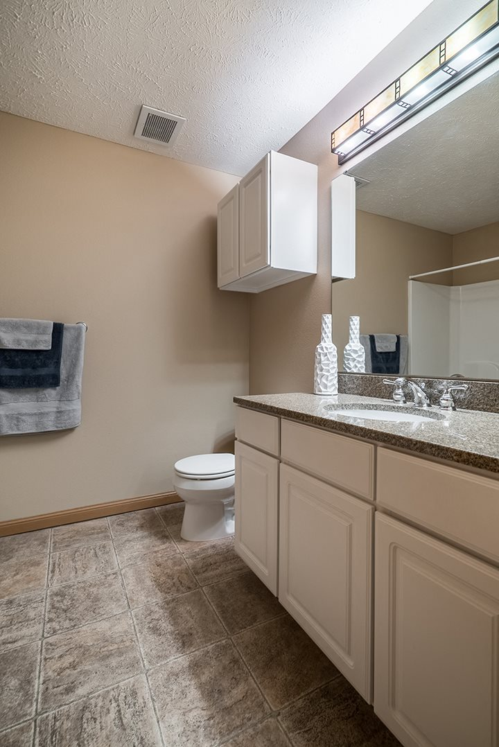Brightly lit, spacious bathroom at Grand Legacy Apartments
