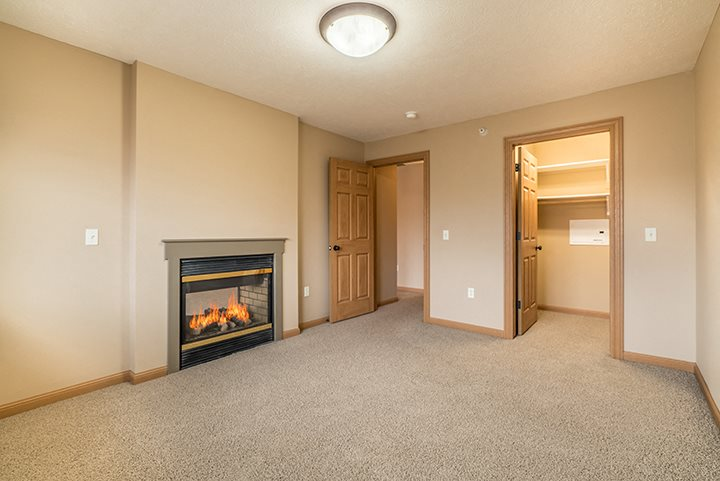 Large master bedroom with closet and fireplace at Grand Legacy Apartments