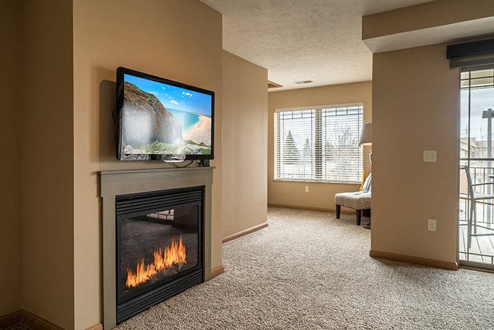 Large living space with fireplace at Grand Legacy Apartments