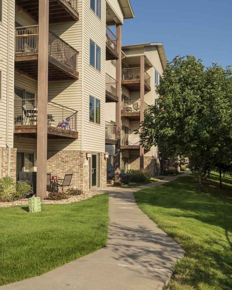 Flats-style apartments with balconies overlooking Zorinsky Lake Park at Grand Legacy apartments and townhomes in west Omaha NE 68130