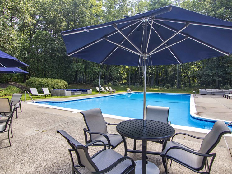 Pool area with lounge chairs and seating areas with umbrellas
