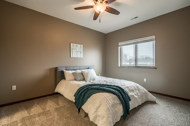 Interiors- Bedroom with ceiling fan amenity at the Villas of Omaha Butler Ridge in Omaha NE