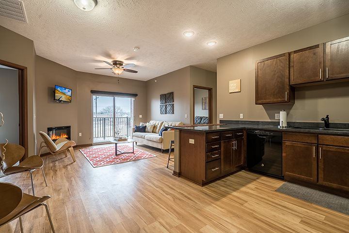 Interiors- Kitchen and living room with hardwood-like flooring at the Villas of Omaha Butler Ridge in Omaha NE