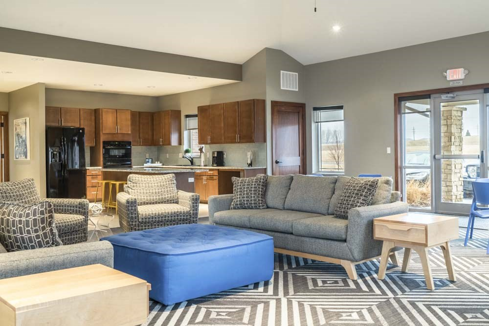 Clubhouse interior with kitchen and seating at Villas of Omaha townhome apartments in northwest Omaha NE 68116