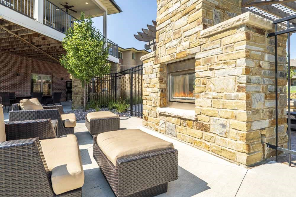 Outdoor fireplace with cushy lounge chairs at Villas of Omaha in northwest Omaha NE 68116