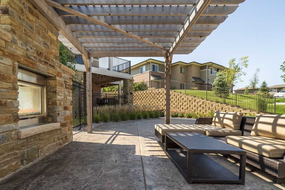 Outdoor fireplace with pergola and seating at Villas of Omaha townhome apartments in northwest Omaha NE 68116