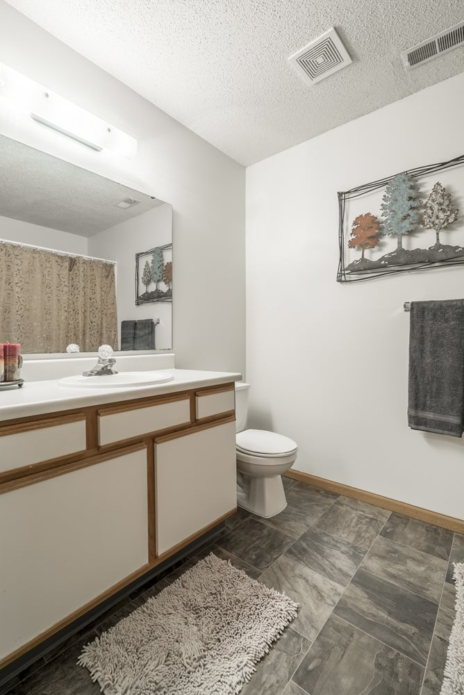 Interiors-Bathroom in non-renovated unit with white and wood cabinetry