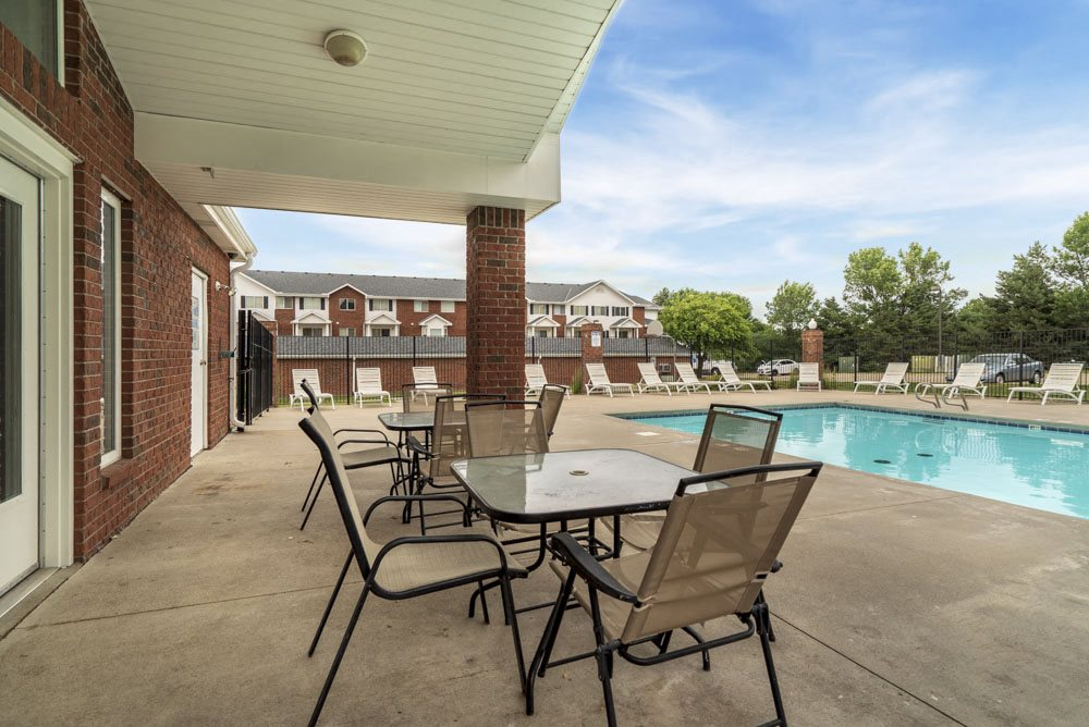 Outdoor seating and tables near the pool at Pine Lake Heights Apartments