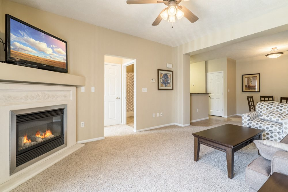 Interiors-Living room with fireplace and ceiling fan at Ridge Pointe Villas
