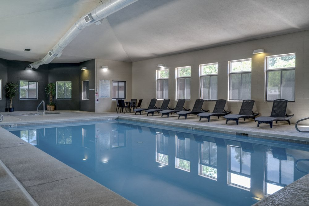 Pool with lounge chairs at Pinebrook Apartments!