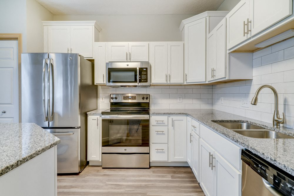 Kitchen with stainless steel appliances, light granite countertops, and while cabinetry at Cascade Pines Duplex and Townhomes