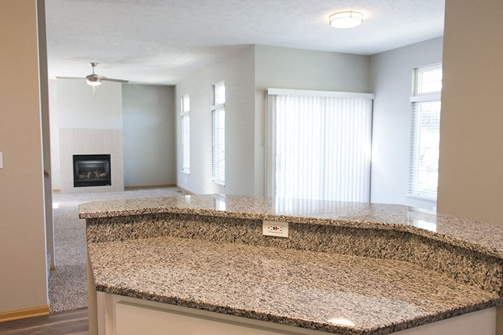 Interiors- Granite island countertop with open-concept dining living room at Cascade Pines Town-homes Lincoln Nebraska