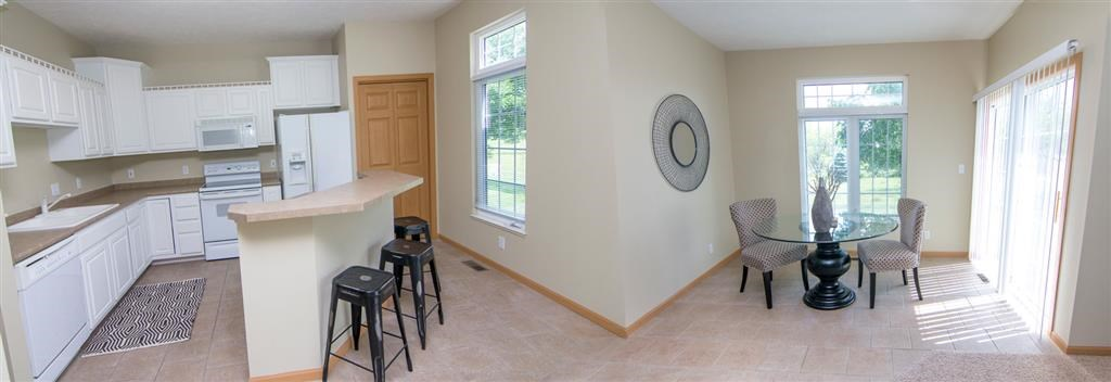 Interiors-Kitchen with Island Bar and Dining Room in Cascade Pines Duplex Homes in Lincoln NE