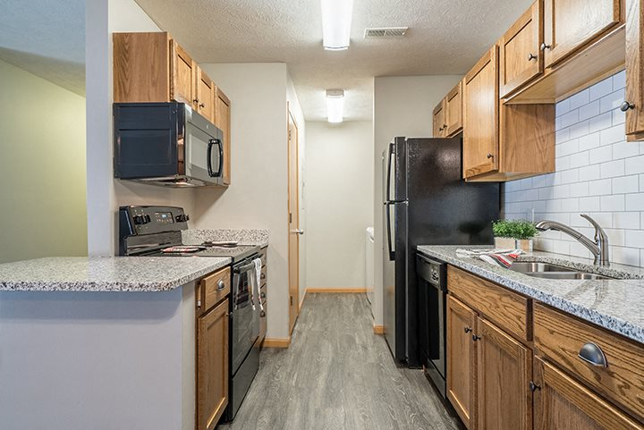 Kitchen with hardwood-style flooring and subway tile backsplash at Williamsburg Park Apartments in Lincoln NE