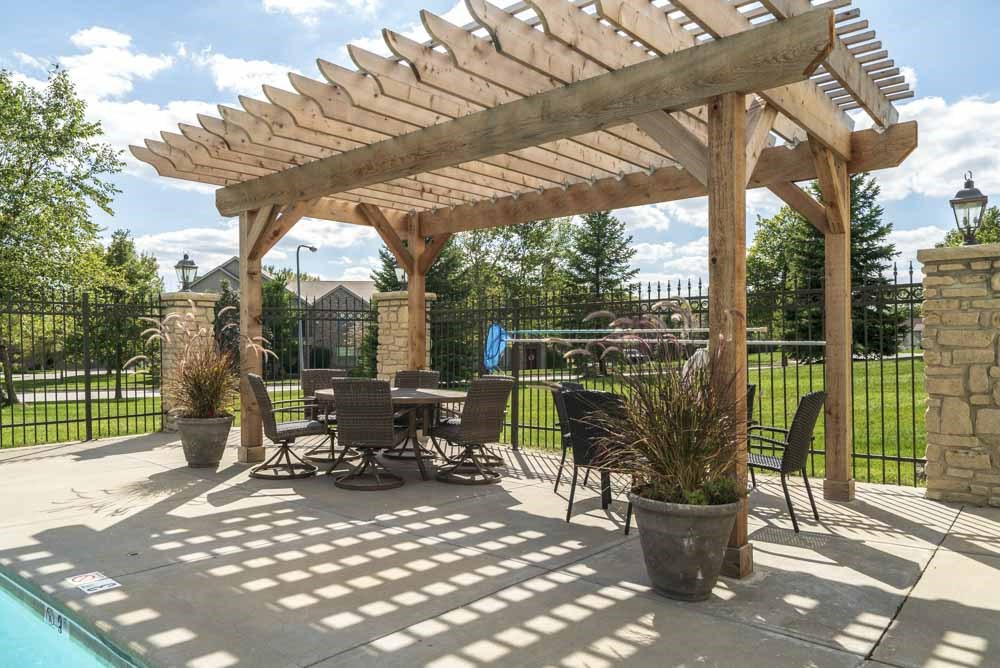 Pergola with seating next to pool at Stone Creek Villas townhomes in west Omaha NE 68116