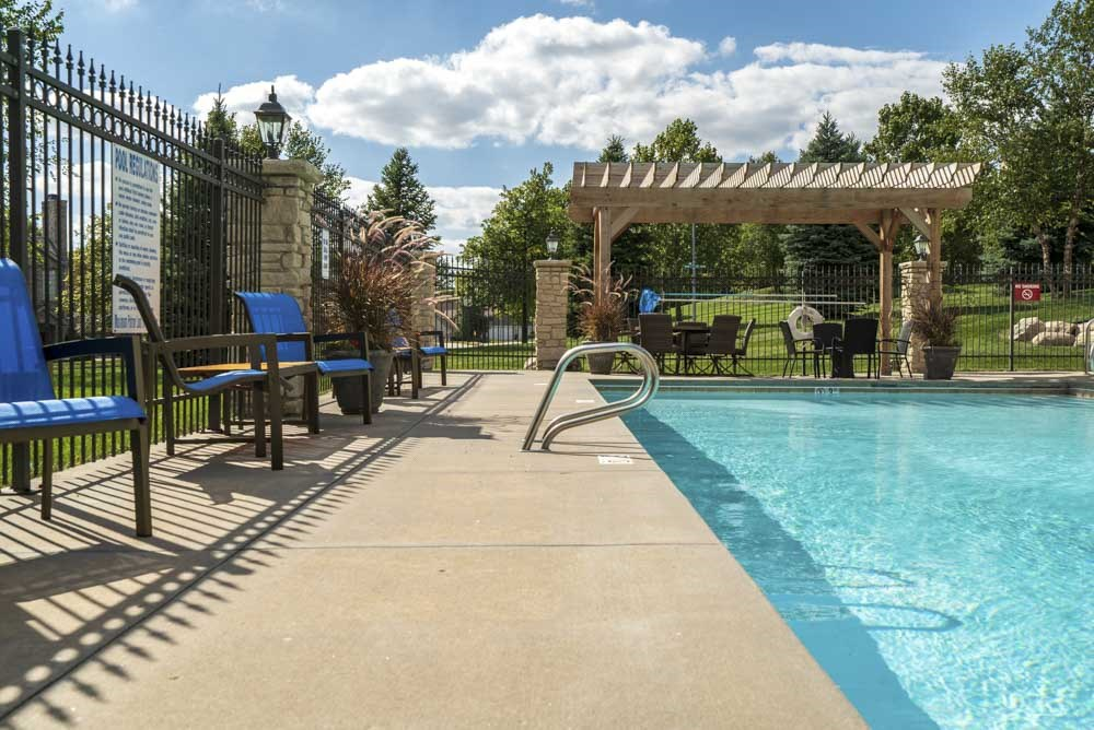 Pergola with swimming pool and chairs at Stone Creek Villas townhomes in west Omaha NE 68116