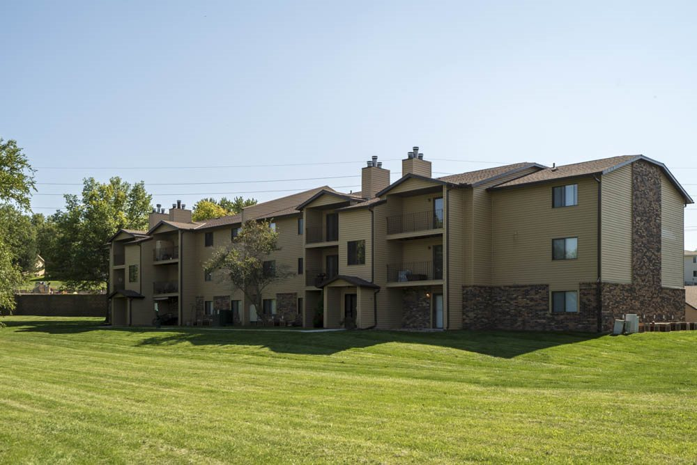 View of greenspace with building exterior at Oakwood Trail Apartments in northwest Omaha, NE, 68164