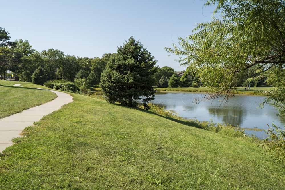 Walking path along Rambleridge Park pond next to Oakwood Trail Apartments in northwest Omaha, NE, 68164