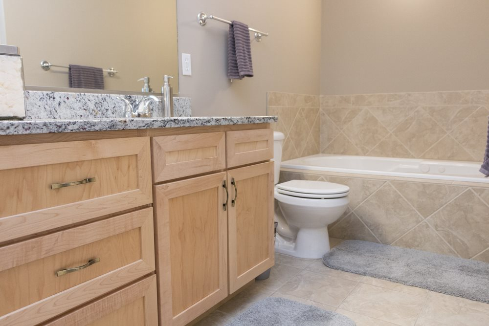 Granite countertops in bathroom with oversized bathtub