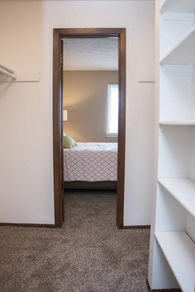 Huge walk-in closet with shelves attached to bedroom