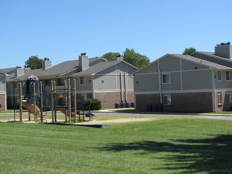 Exterior with playground at Hearth Hollow Apartments in Derby, KS