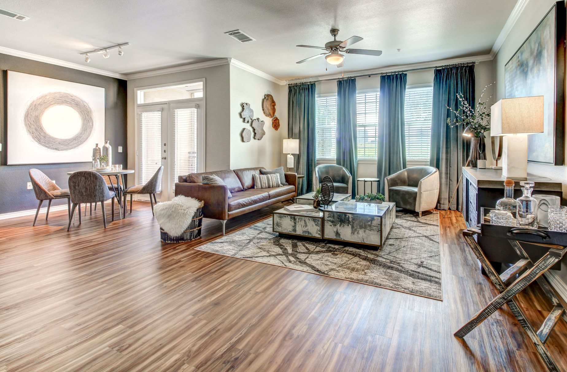 Beautiful open, living room and dining room with faux wood floors and natural light.