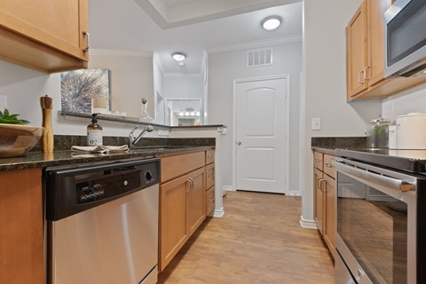 Maple Spice or Dark Cherry Cabinets With Brushed Nickel Hardware and Stainless Steel Kitchen Appliances.