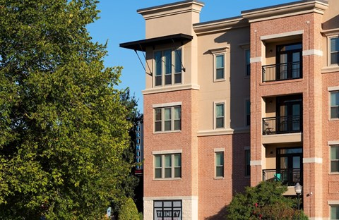 Four story brick building with patios and balconies.