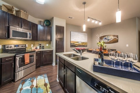 Luxurious kitchen, stainless steel appliances, stunning large islands and faux wood flooring.