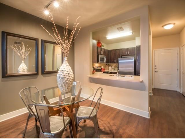 Spacious dinning room with faux hardwood floors, beautiful natural light and open floor plan.