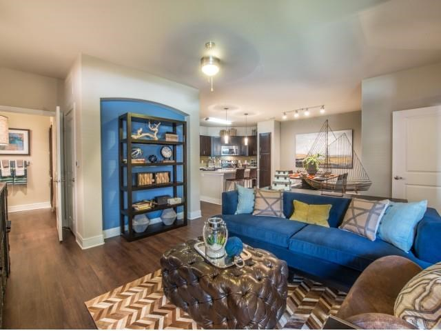 Spacious living room with faux hardwood floors, beautiful natural light and open floor plan.