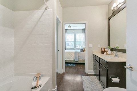 Spacious bathroom, with framed mirror with luxury tub/shower combo.