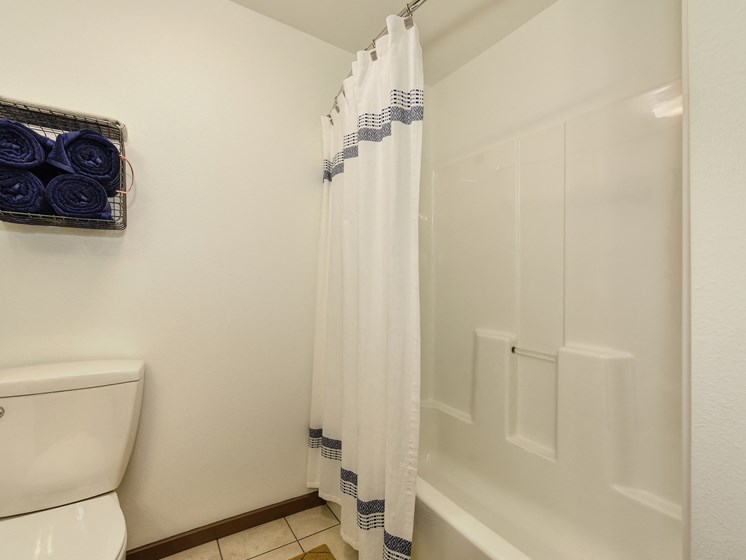 Bathroom with Tiled Floor, Toilet and White Curtains