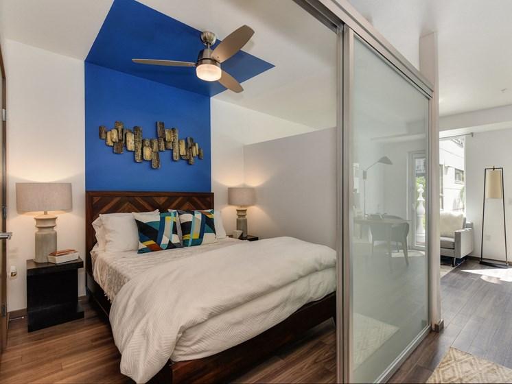 Bedroom  with Sliding Door, Hardwood Inspired Floor, White Comforter Bedding, Blue Wall and Ceiling Fan/Light