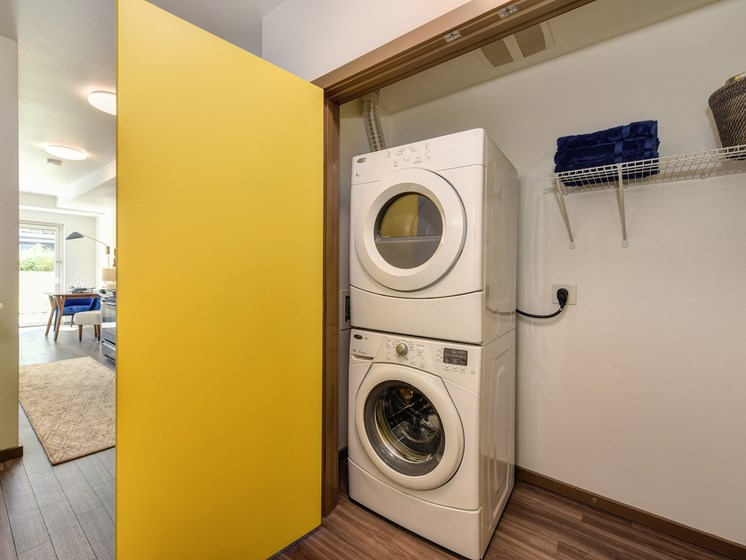 In Unit Laundry with Dryer Stacked On Top of Washer, Yellow Door and Hardwood Inspired Floors